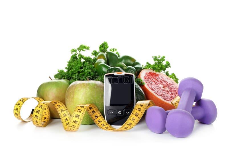 与测量的磁带、哑铃和健康食品的数字glucometer在白色背景 糖尿病饮食 库存照片