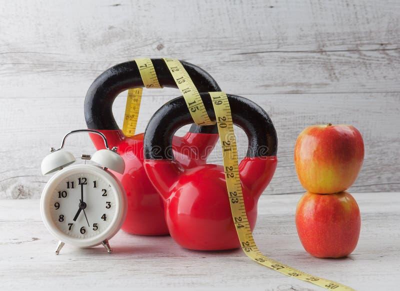 与测量的磁带、苹果和时钟的两红色kettlebells 库存图片