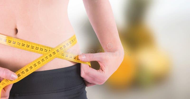 与测量的磁带的妇女测量的重量在夏天海滩的腰部 库存照片