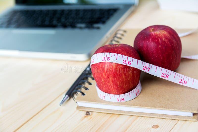 与测量的磁带的红色苹果在笔记本 库存照片