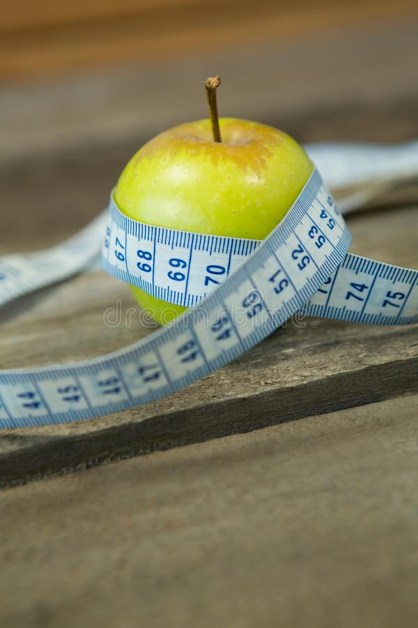 与测量的磁带的绿色苹果在木桌上 免版税图库摄影