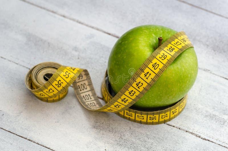 与测量的磁带的绿色苹果在白色木背景 饮食 免版税库存图片