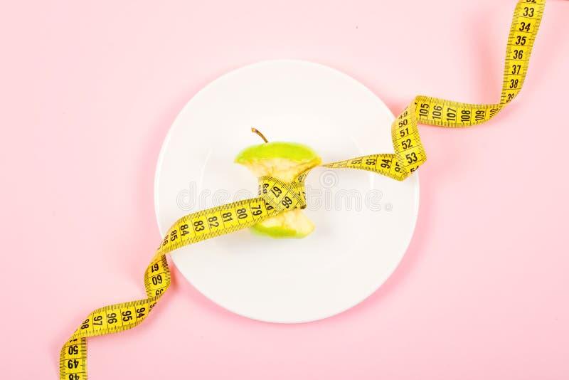 与测量的磁带的苹果计算机核心在一块白色板材的腰部位置在桃红色背景 节食,斟酌损失,饥饿,健身 图库摄影