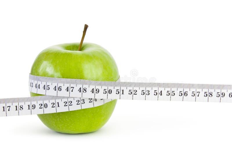 与测量的磁带的苹果计算机 库存图片