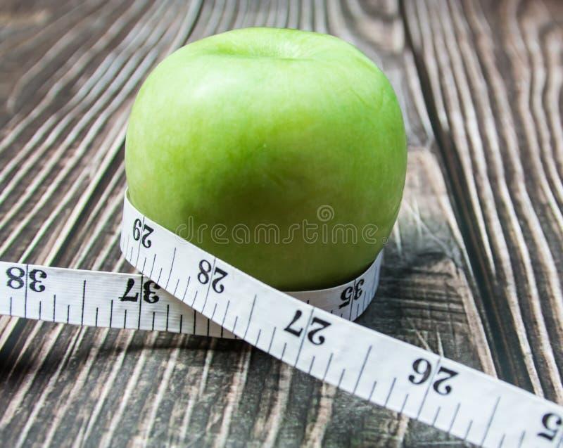 与测量的绿色苹果在木头 库存照片