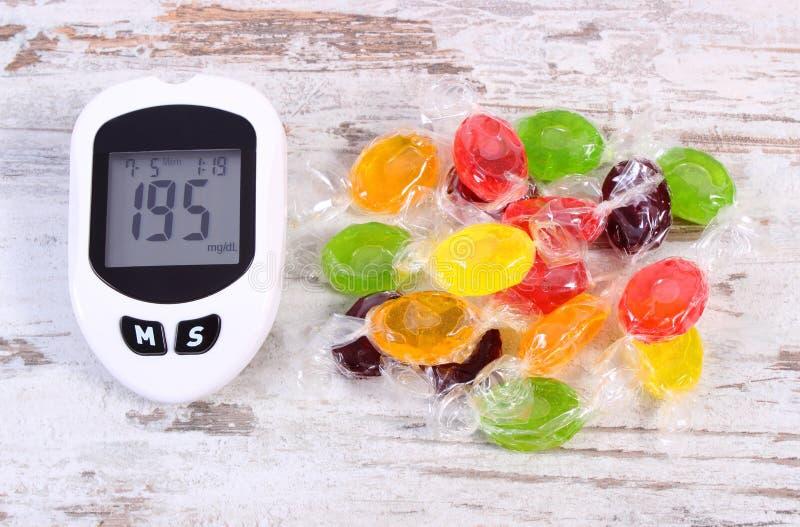 与测量糖水平和五颜六色的糖果,减少吃甜点概念的坏结果的Glucometer 库存图片
