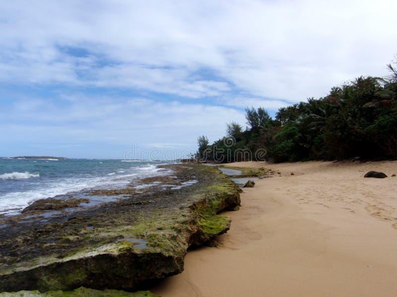 与浪潮水池和大岩石的海滩 库存照片