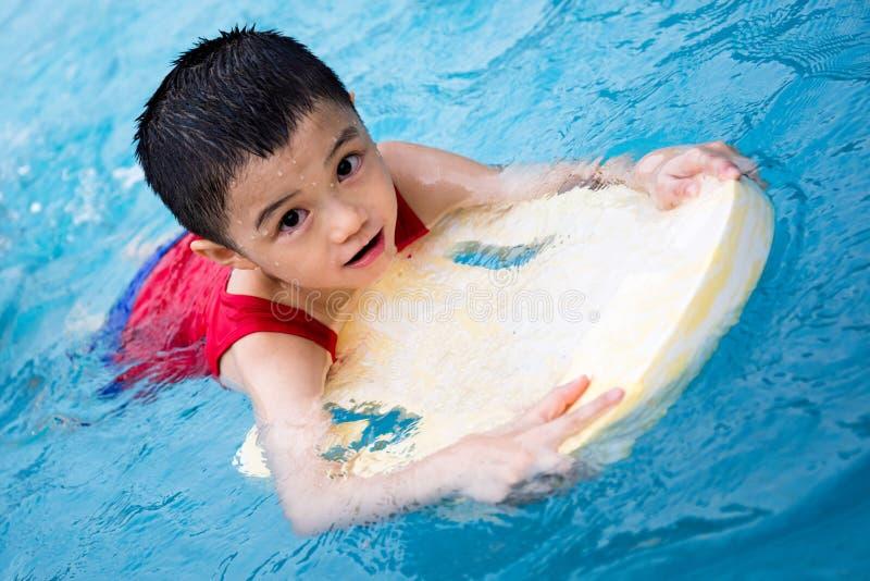 与浮动委员会的亚洲中国小男孩游泳 库存图片