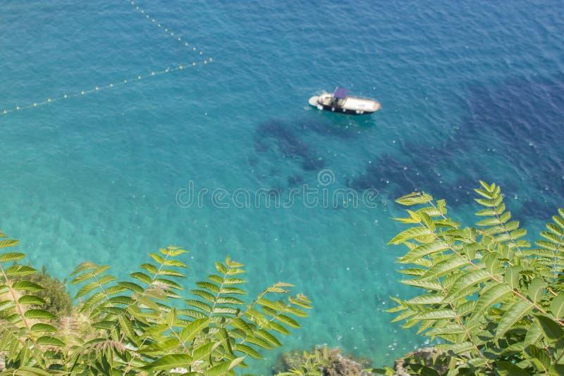 与浮动小船的被弄脏的热带水 库存照片