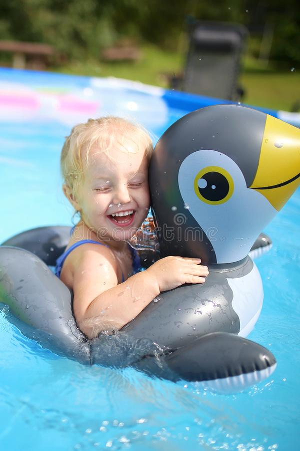 与浮动木筏的笑的女婴游泳在后院Swimmi 图库摄影
