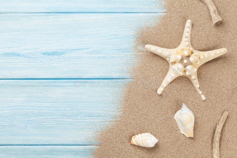 与海星和壳的海沙在木头 免版税图库摄影
