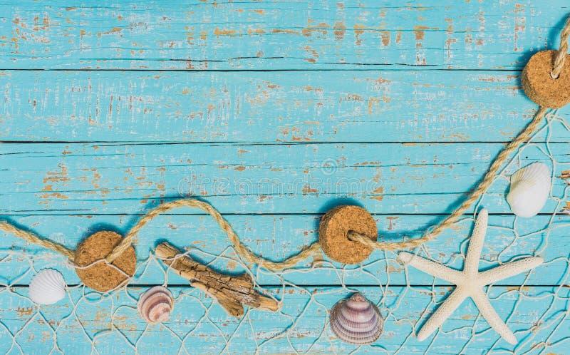与海星和贝壳的海海背景在土耳其玉色木头的捕鱼网 免版税库存图片