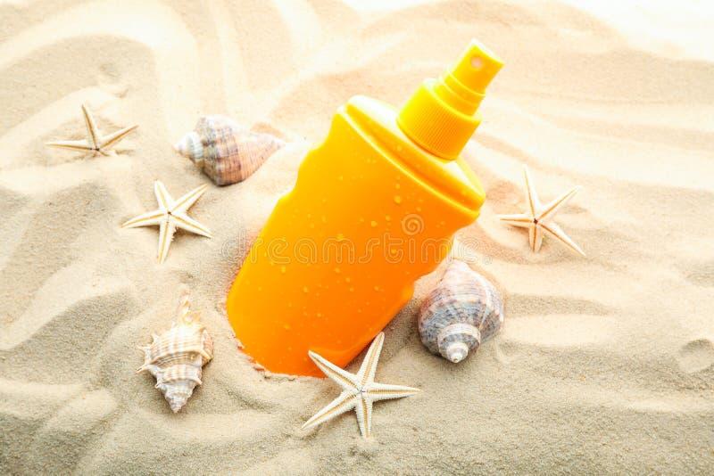 与海星和贝壳的遮光剂在清楚的海沙,特写镜头 免版税库存图片