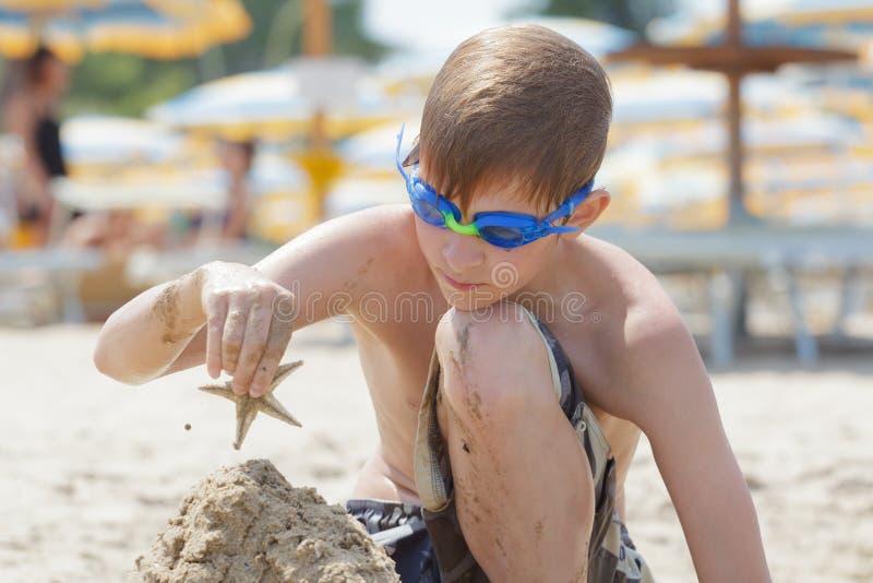与海星的被集中的海滩男孩大厦沙子城堡在上面 图库摄影