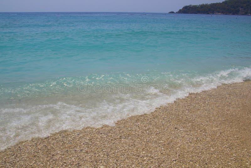 与海泡沫的大海 小波浪来临到岸 与白色小卵石的绿松石水在海滩 水平线遇见 免版税库存图片