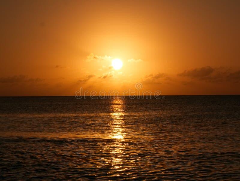 与海洋反射的明亮的金子日落 免版税库存照片