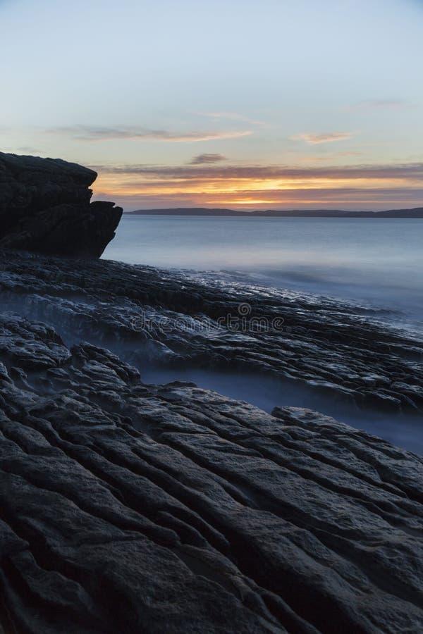 与海洋的长的曝光日落岩石的 库存图片