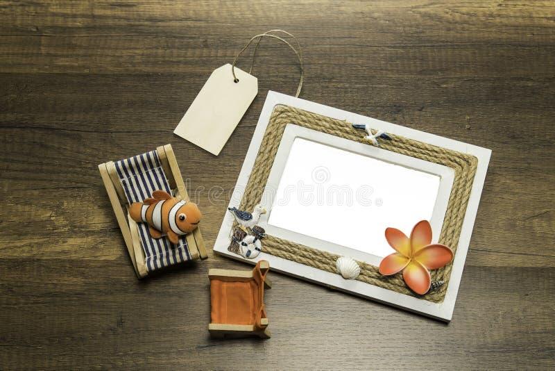 与海滩床和椅子的一个照片框架和在木桌上的价牌 免版税库存照片