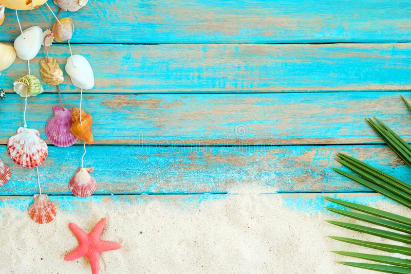 与海滩沙子、starfishs垂悬在蓝色木背景的椰子叶子和壳装饰的夏天背景 免版税库存照片
