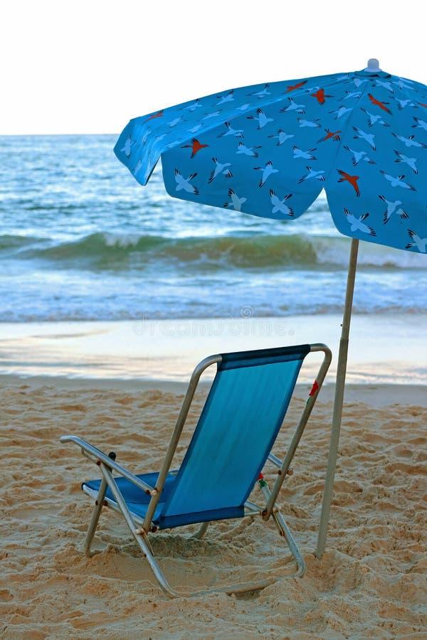 与海滩遮光罩的充满活力的蓝色海滩睡椅在面对大西洋的沙滩 免版税库存图片