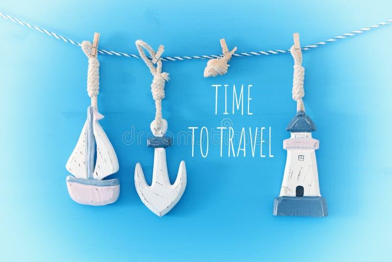 与海生活方式装饰的船舶概念:垂悬在串的帆船和船锚在蓝色木背景 库存照片