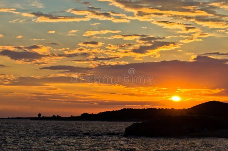 与海的剪影的美丽如画的cloudscape晃动在日落 免版税库存照片