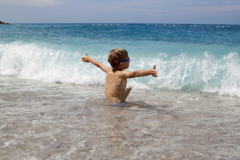 与海的splahes波浪的孩子戏剧 免版税库存照片
