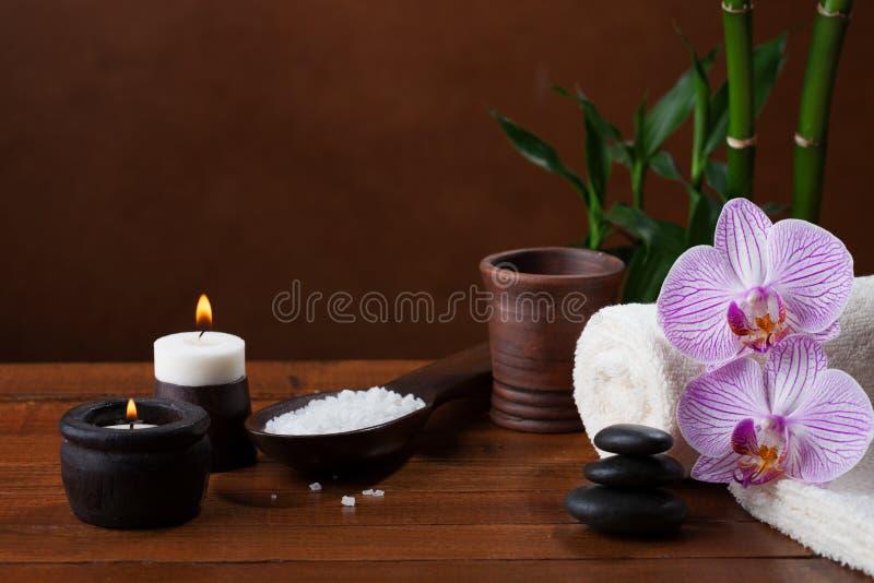 与海盐、蜡烛、毛巾、石头和兰花的温泉设置 免版税库存图片