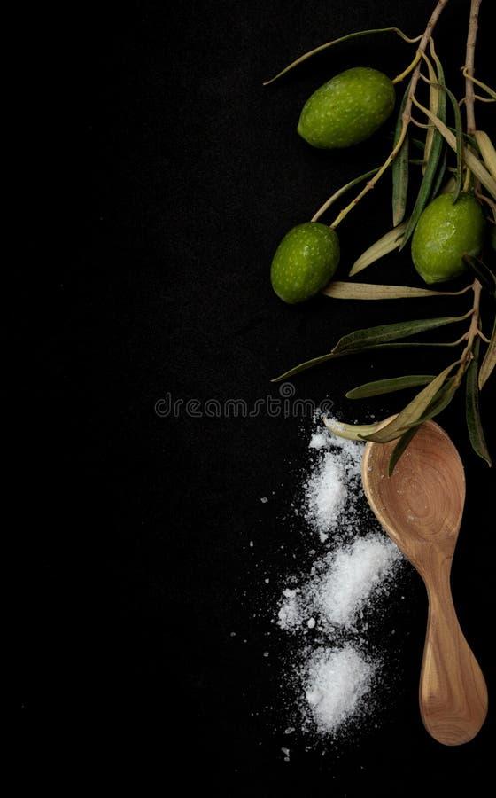 与海盐和木匙子的绿橄榄在黑背景 免版税库存图片