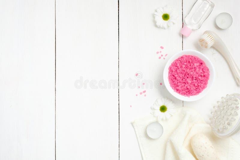 与海盐的温泉设置在碗,毛巾,按摩工具,春黄菊花,在woode背景,顶视图的蜡烛 健康 库存照片