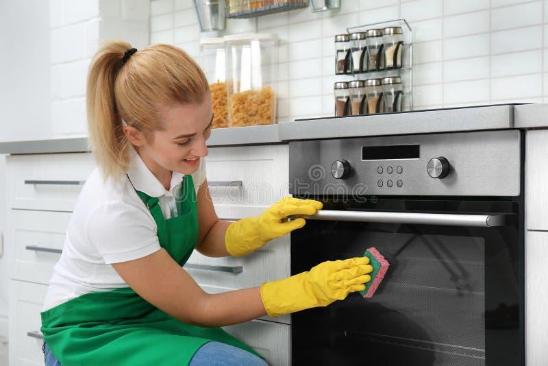 与海绵的女性管理员清洁烤箱 库存图片