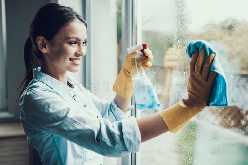 与海绵的年轻微笑的妇女洗涤的窗口 免版税库存图片