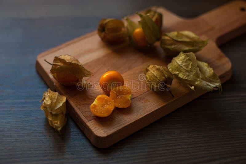 与海角的新鲜的空泡莓果在一个木切板与 免版税库存图片