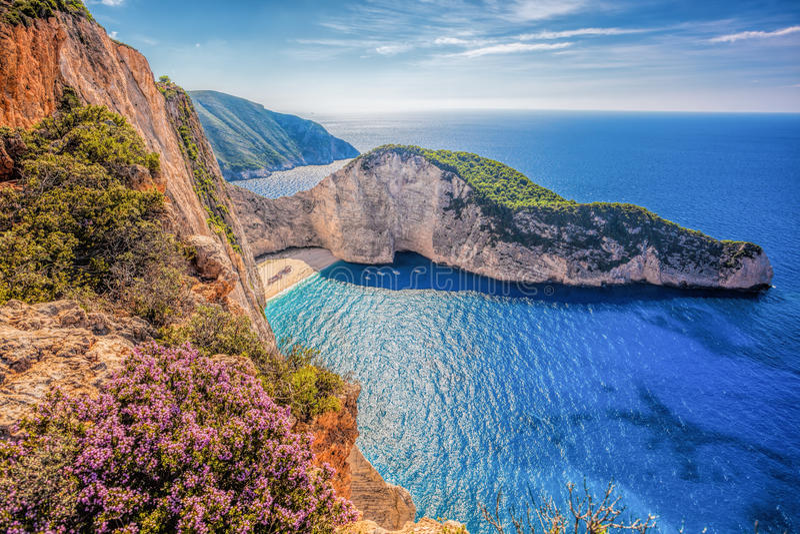 与海难和花的Navagio海滩反对在扎金索斯州海岛上的日落在希腊 库存图片