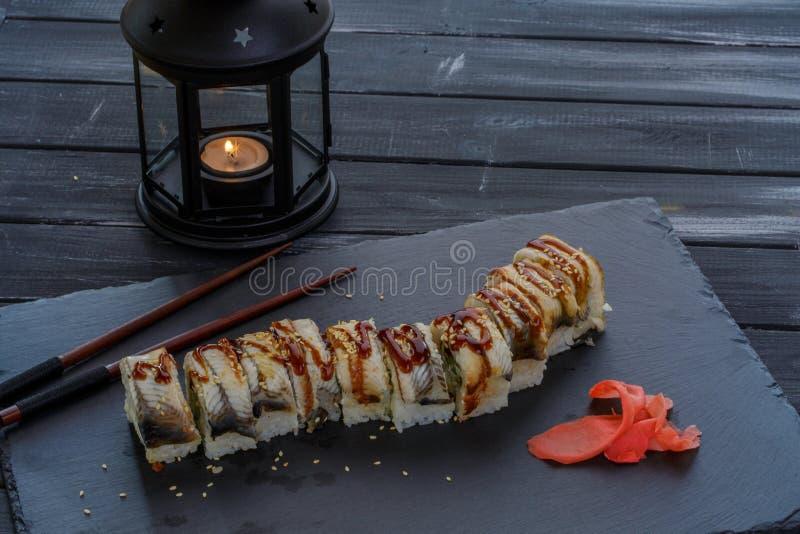 与海鲜和鳗鱼鱼的鲜美和可口传统日本寿司卷在与蜡烛的黑背景 免版税库存照片