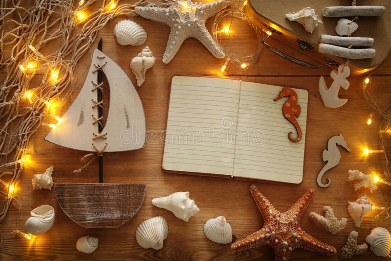 与海洋生活样式的船舶概念在木桌上反对 免版税图库摄影