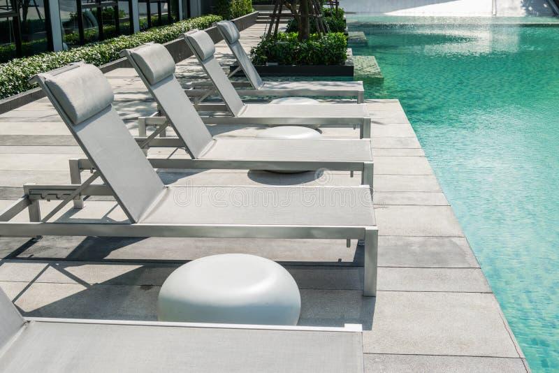 与海滩睡椅的游泳池 库存图片