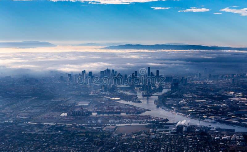 与涌现从早晨雾的摩天大楼的墨尔本地平线 图库摄影