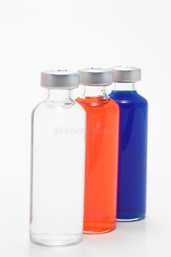 与液体的三个玻璃小瓶 免版税库存照片
