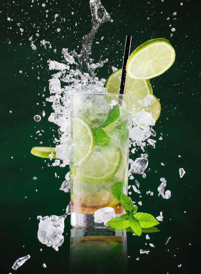 与液体飞溅的新mojito饮料和在结冰行动的被击碎的冰 库存图片