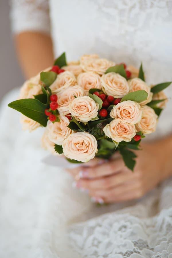 与淡粉红的玫瑰和莓果的婚礼花束 图库摄影