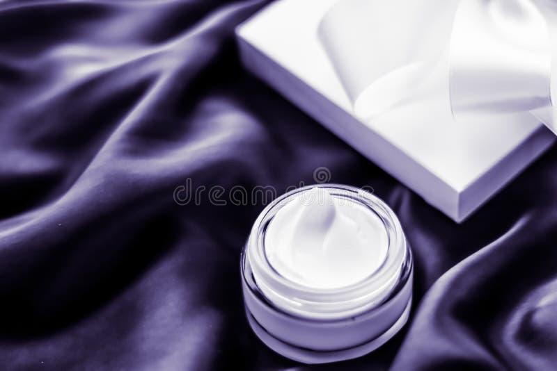 与淡紫色气味的豪华润湿的面霜在紫罗兰色丝绸,skincare秀丽 免版税库存图片