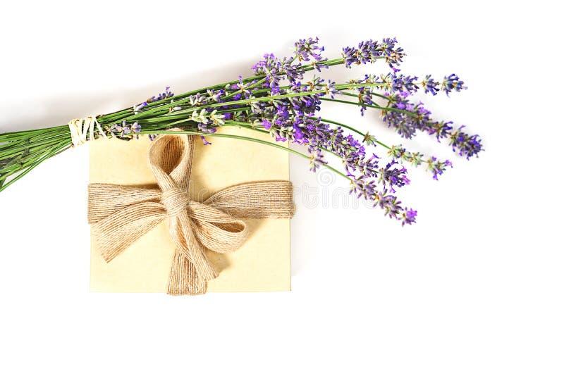 与淡紫色花和礼物盒自然颜色的秀丽设置与在白色背景的弓,被隔绝 免版税库存照片