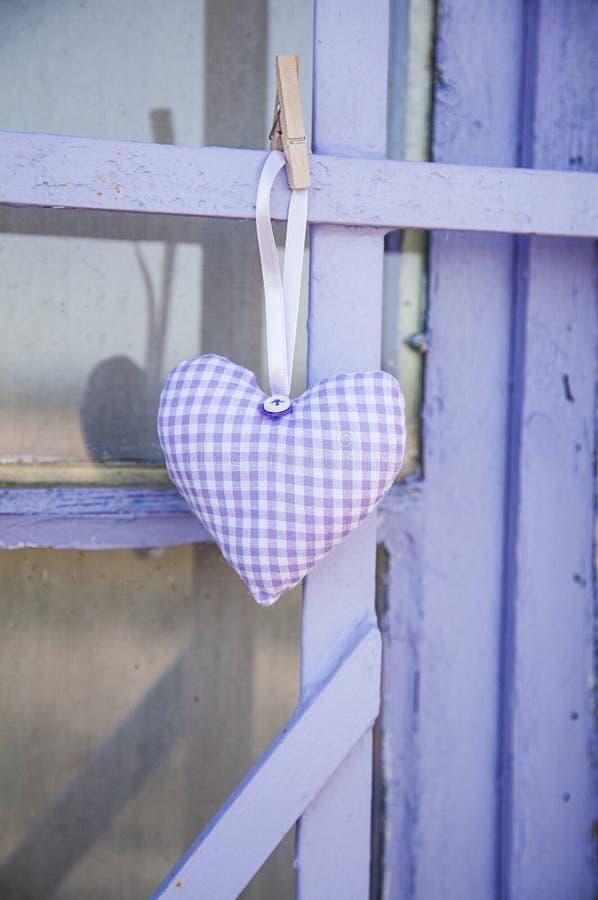 与淡紫色花的俏丽的手工缝制的织品心脏 库存照片