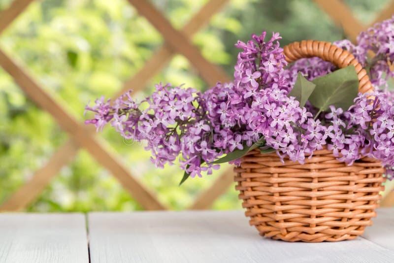 与淡紫色花花束的篮子在一张白色木桌上的在summerhouse在庭院里 免版税图库摄影