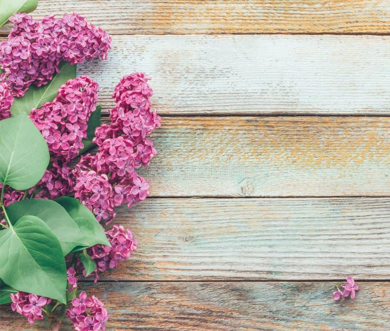 与淡紫色花花束的春天背景在木板条的 免版税库存图片