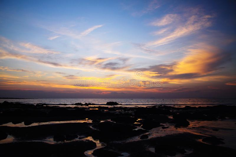 与深垂悬的暴风云和湿烂泥的天空在黄色和红色明亮的光裹的低潮期间在日落期间 库存照片