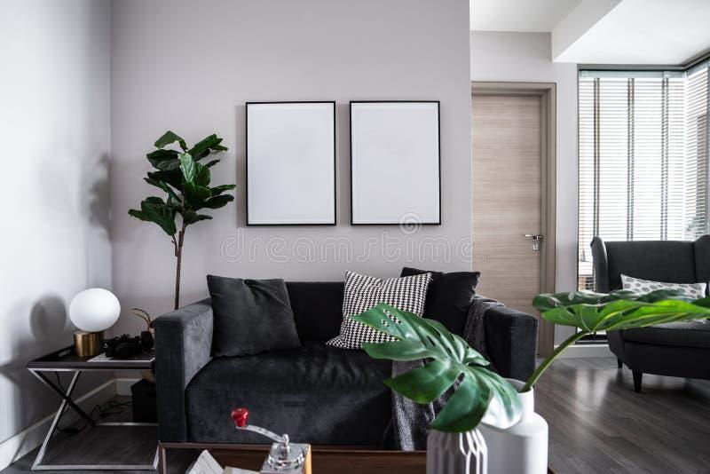 与深灰天鹅绒织品沙发、人为安装在墙壁/coz的植物和空的相框的舒适客厅角落 图库摄影