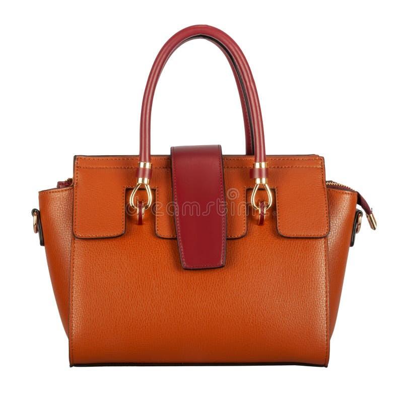 与深紫红色插页和把柄的橙色女性皮包 免版税库存图片
