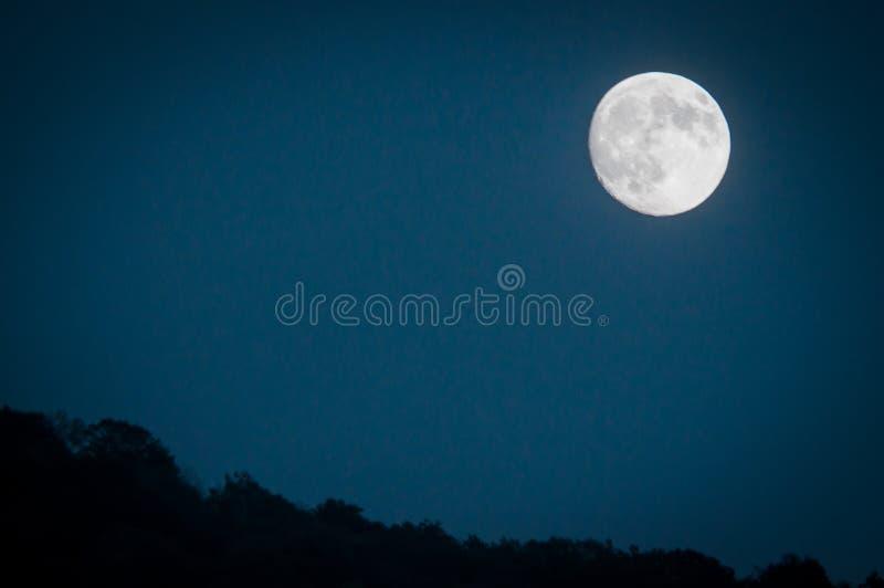 与深蓝色夜间天空和层状小山的剧烈的山月亮上升在距离 库存照片